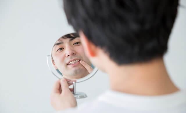 歯並びを鏡でチェックしている男性