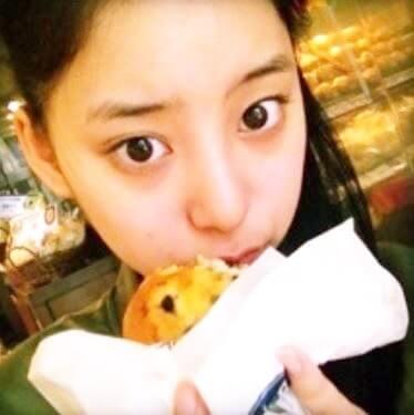 外でパンを食べるモデル・新木優子