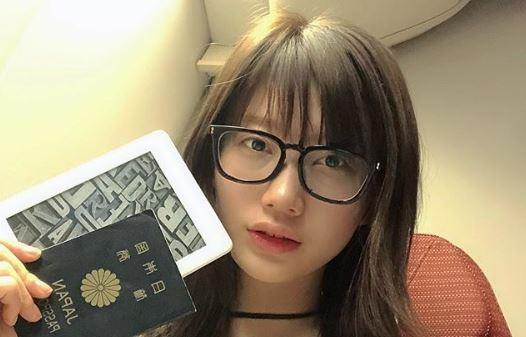 パスポートとキンドルを持つモデル・小倉優香