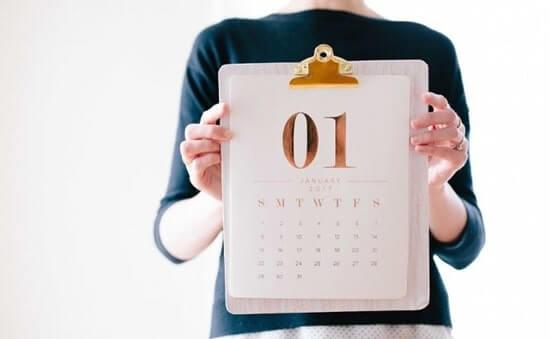 1月のカレンダーを持つ女性