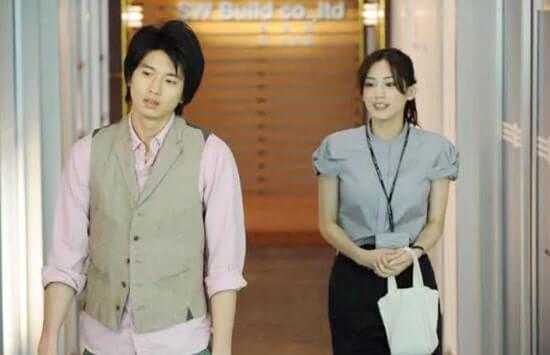 会社の廊下を歩く男性と女性