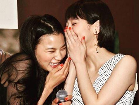 口を手で覆って笑う2人の女性