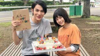 屋外でケーキを持つ中川大志と杉咲花