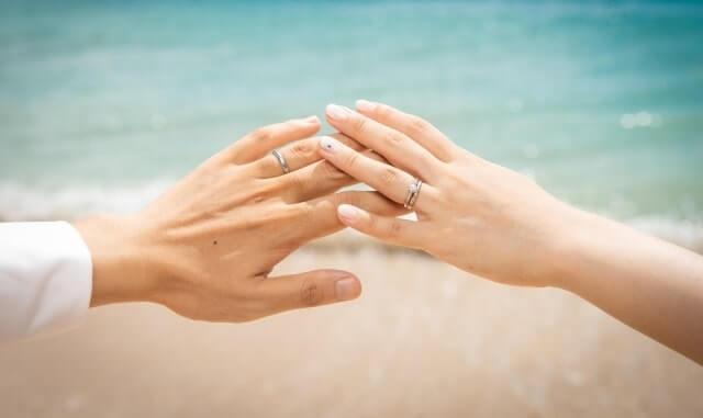 海辺で手を重ねる夫婦