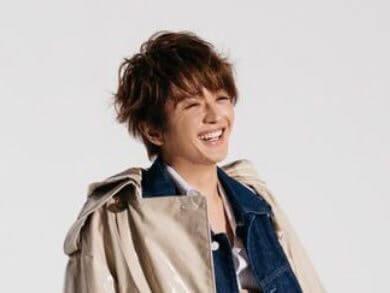 グレーのジャケットを着ている歌手・西島隆弘