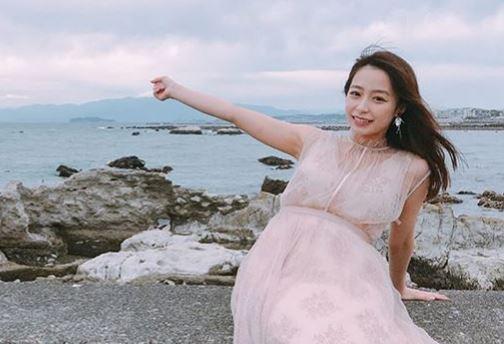 海岸の塀に座るフリーアナウンサー・宇垣美里