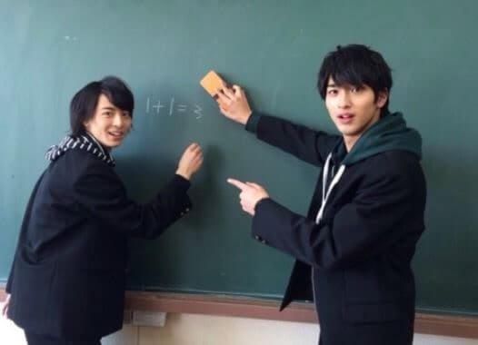 学校の黒板を使う2人の男子学生