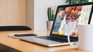 ノートパソコンとコーヒーがテーブルに置いてある