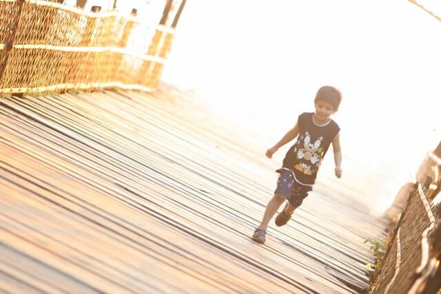 橋を走って渡る少年