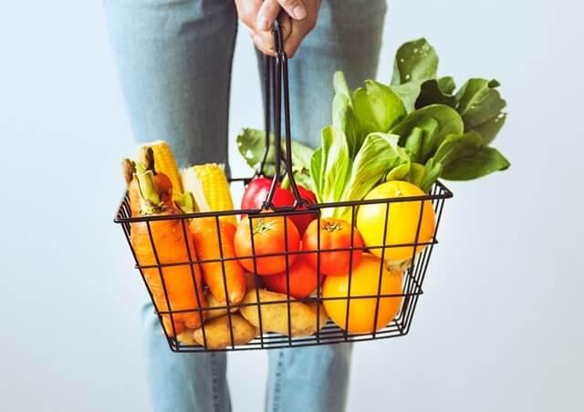 野菜の入ったカゴを持つ女性